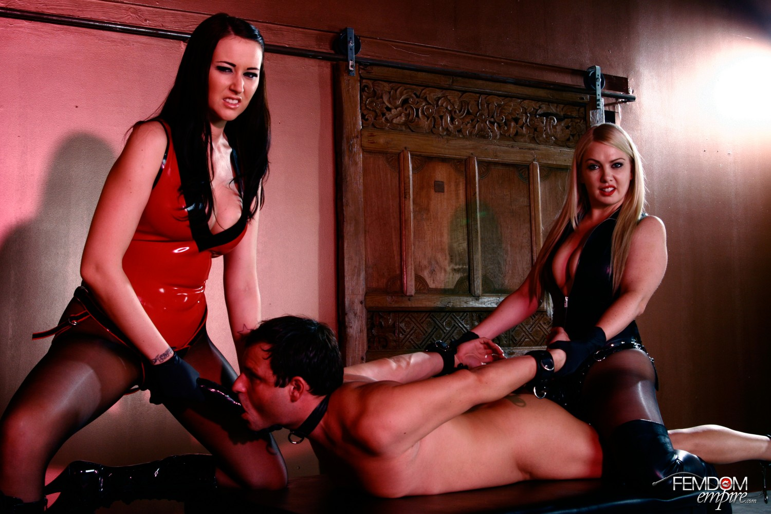 Dominatrixes Alexis Grace and Lexi Sindel love demeaning their mega-slut as they fill his jaws and bootie with their strap on dildo dicks.